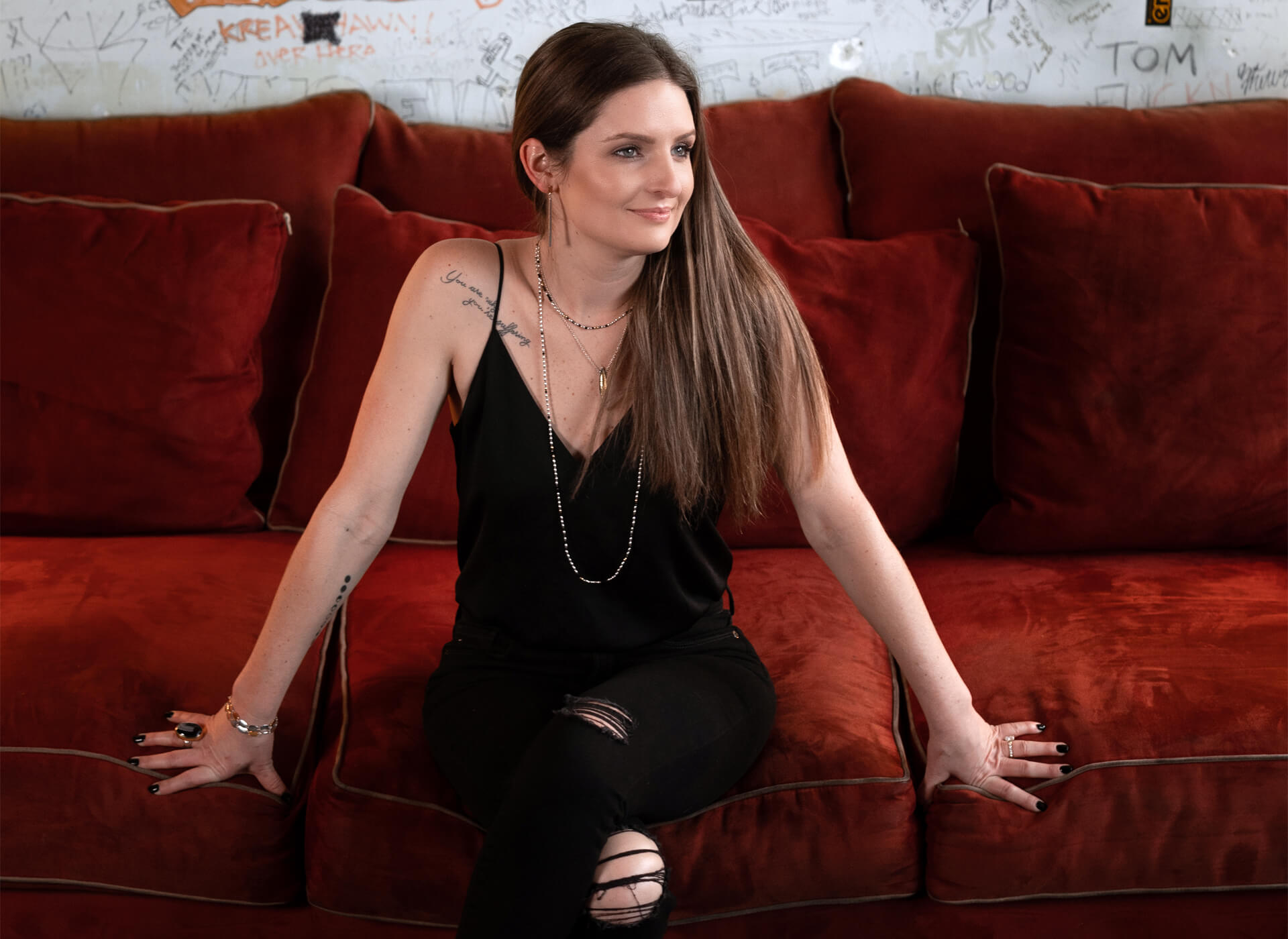 Young woman with long brown hair pulled to one side, is wearing a black tank top and sitting on a wide red velvet couch.
