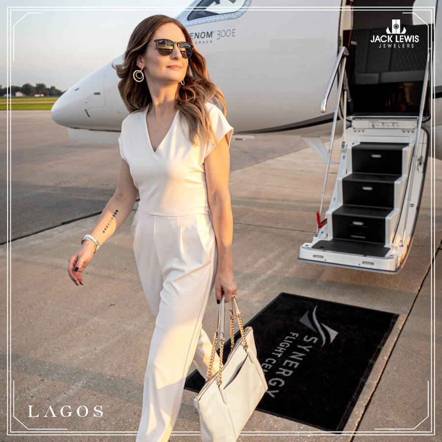 Young woman with long brown hair wearing a white pantsuit, sunglasses and holding a large white purse, while walking away from an airplane wing as she looks to the sunset in the distance. She is wearing a bracelet, earrings and rings from the brand Lagos and their caviar collection.
