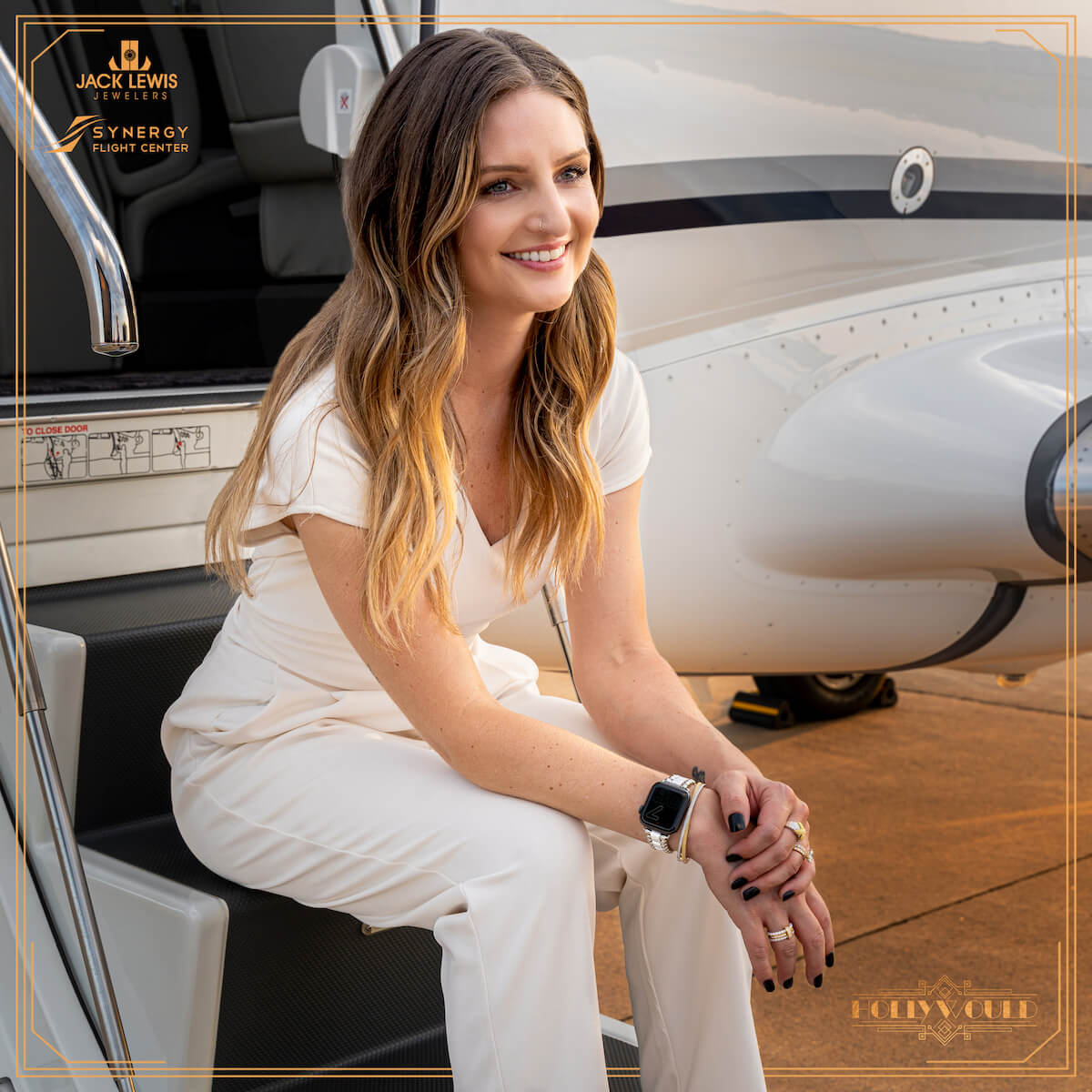 Young woman with long brown hair wearing a white pantsuit, and sitting on airplane steps with the sunsetting behind her. She is wearing a bracelet, earrings and rings from the brand Lagos and their caviar collection.