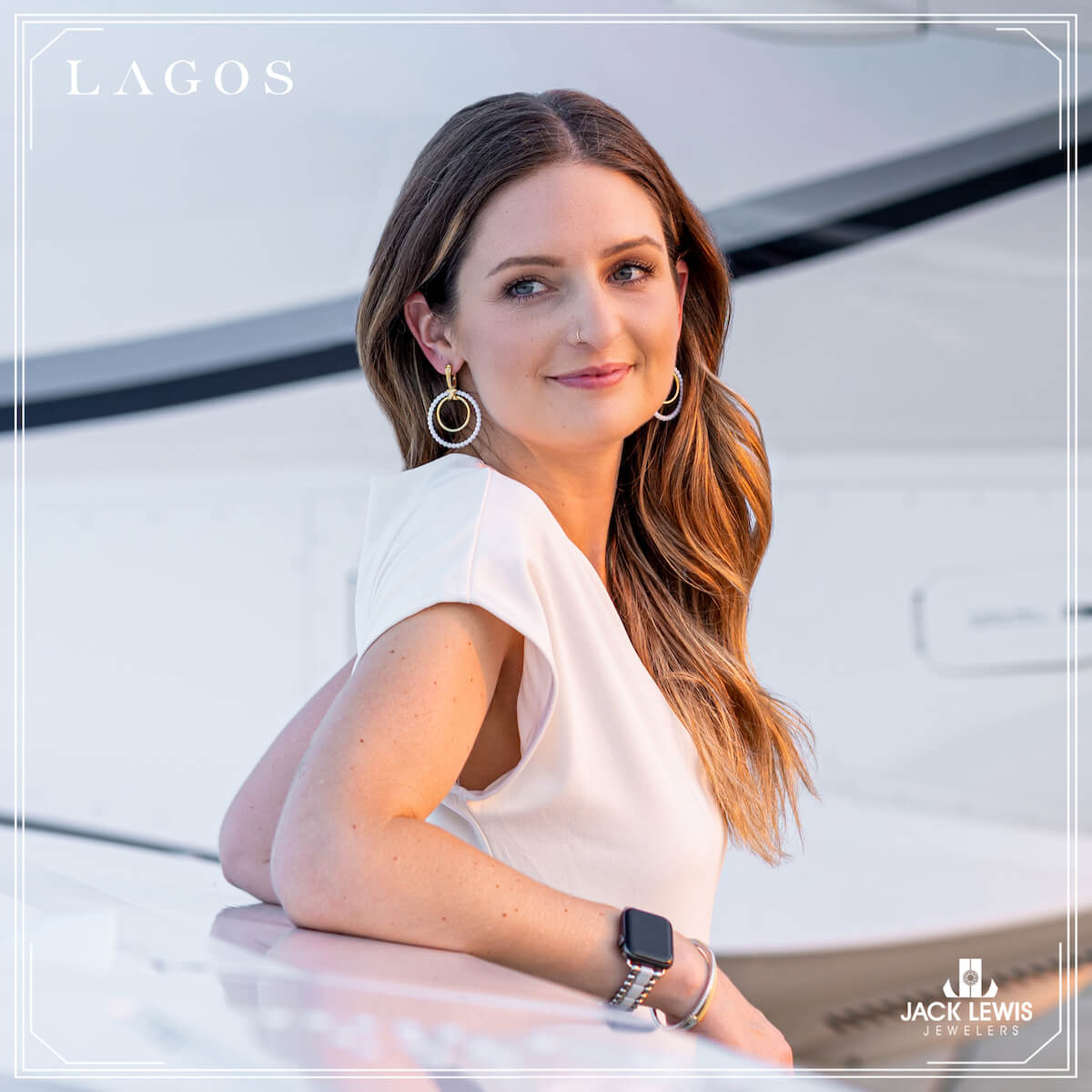 Young woman with long brown hair wearing a white pantsuit, and leaning against an airplane wing looking over her shoulder into the camera. She is wearing a bracelet, earrings and rings from the brand Lagos and their caviar collection.