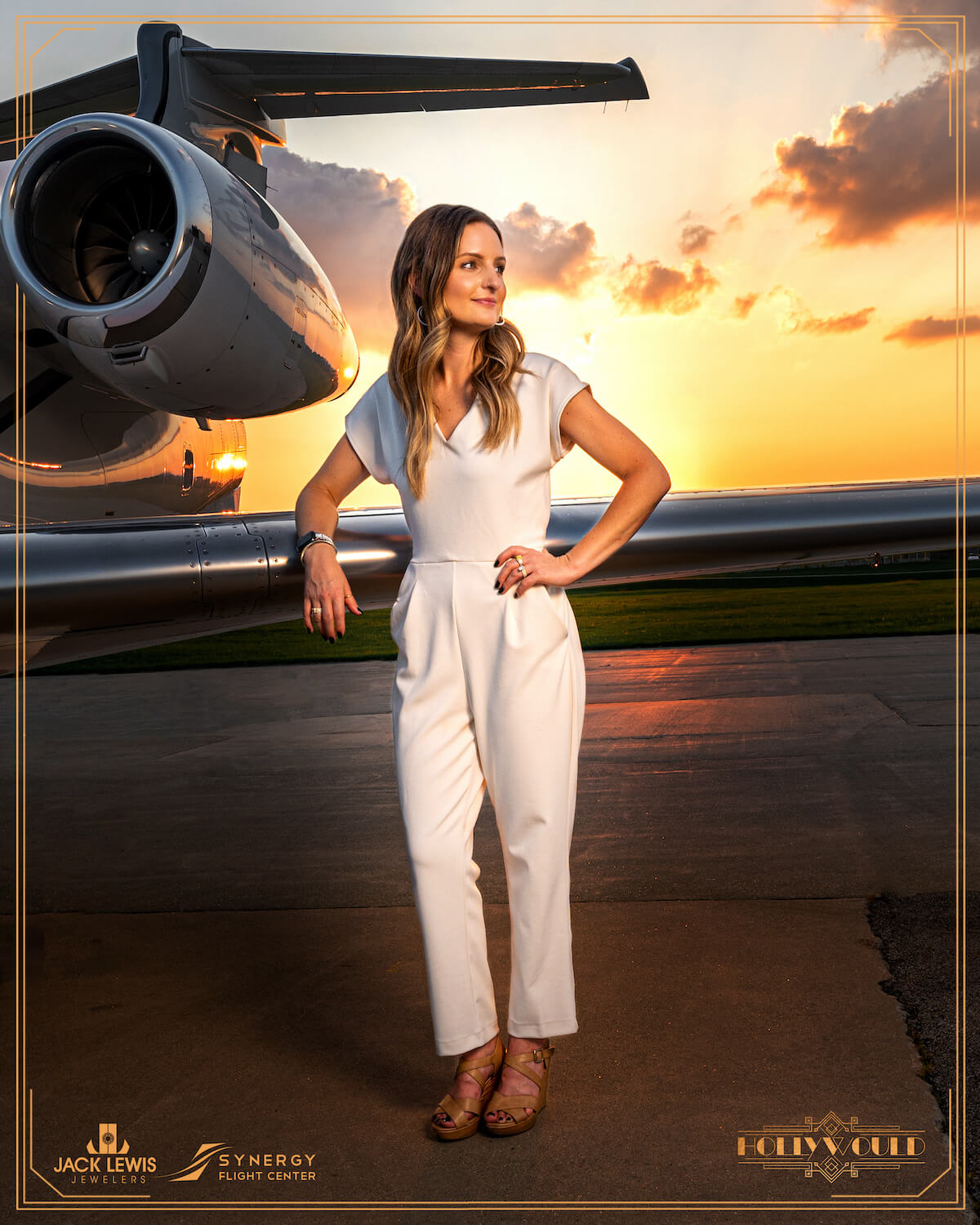 Young woman with long brown hair wearing a white pantsuit, and standing in front of an airplane wing with the sunsetting behind her. She is wearing a bracelet, earrings and rings from the brand Lagos and their caviar collection.