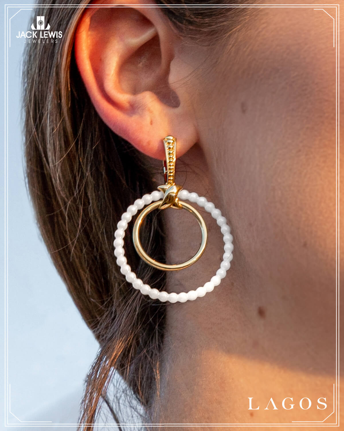 Close up shot of LAGOS hoop earrings with interchangable colors, currently displayed in white and gold. Being worn by a young woman with long brown hair.