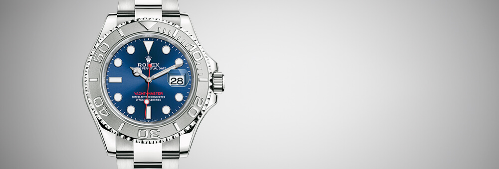 The ROLEX Oyster Perpetual Yacht-Master 40 in Oystersteel and platinum with an Oyster bracelet. This model features a bright blue dial and a bidirectional rotatable bezel in platinum with a raised 60-minute graduation and numerals. The second hand is red.