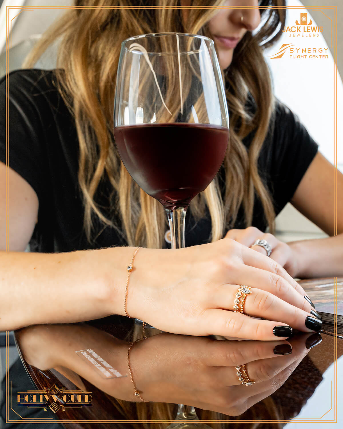 A young woman with long brown hair is reading a magazine from her airplane seat alongside a glass of red wine. This is a close up of her hands where you can see Debeers Forevermark jewelry including a diamond bracelet and two diamond rings.