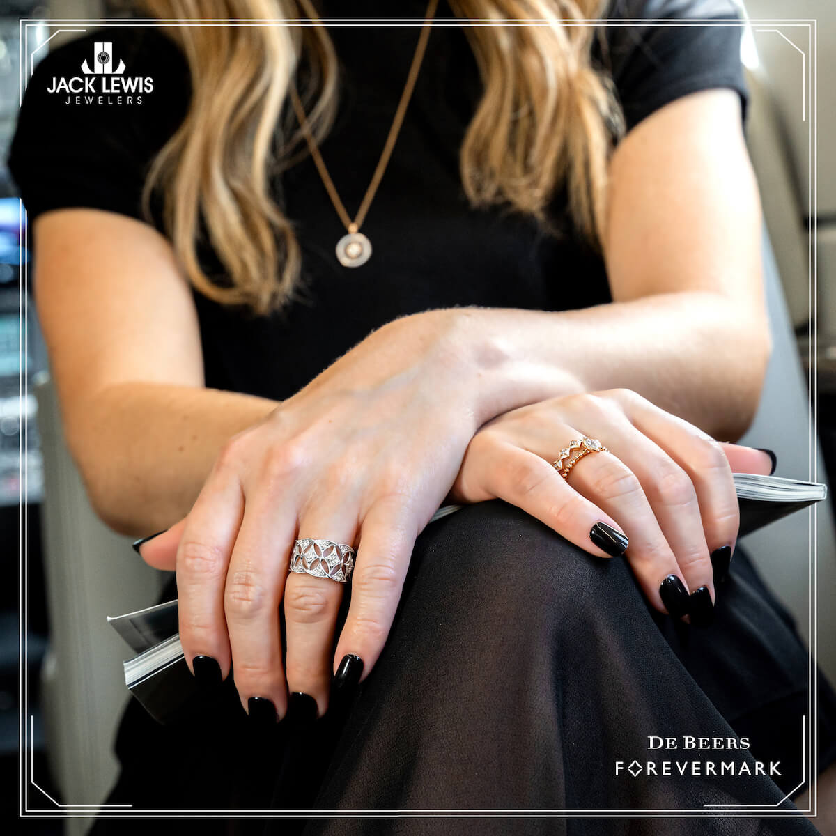 Close up of a young woman's hands with black fingernails and wearing Debeers Forevermark Rings in white gold and yellow gold