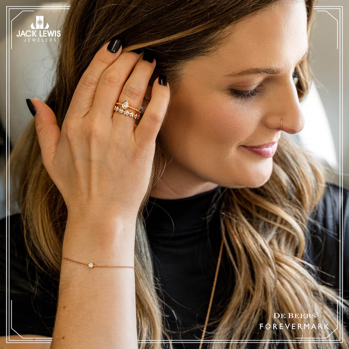 Close up of a young woman with long brown hair seating in a private yet. She is brushing her hair back and you see two gold and diamond rings on her hand from Debeers Forevermark.
