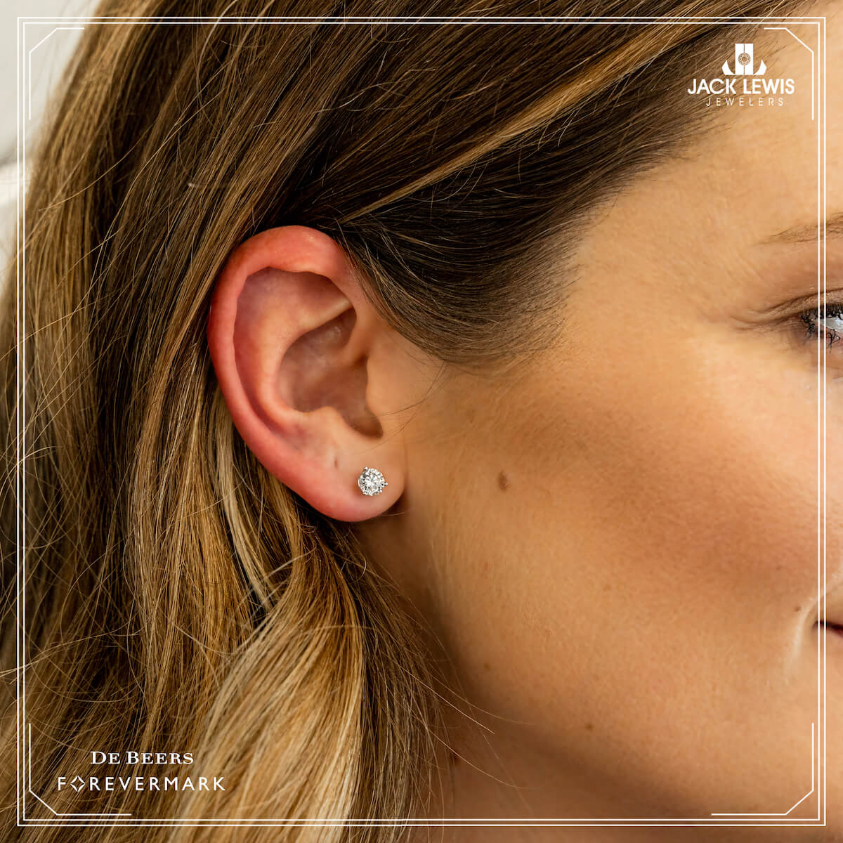 Close up of a diamond stud earring by Debeers Forevermark being worn by a young woman with long brown hair
