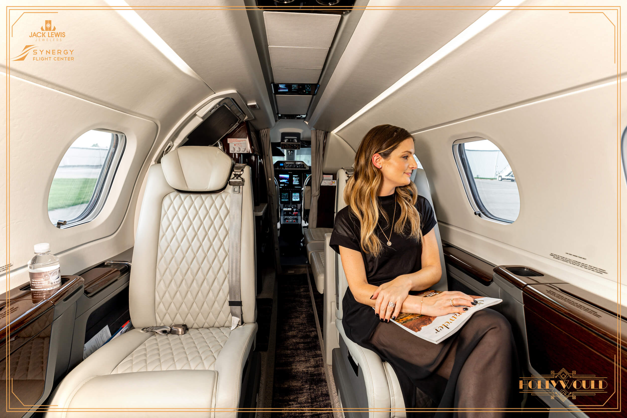 Young woman with long brown hair seated in a private jet at the Synergy Flight Center in Bloomington Illinois. She is wearing a black dress and looking out the window at the runway. Jewelry by Debeers Forevermark is clearly in view.