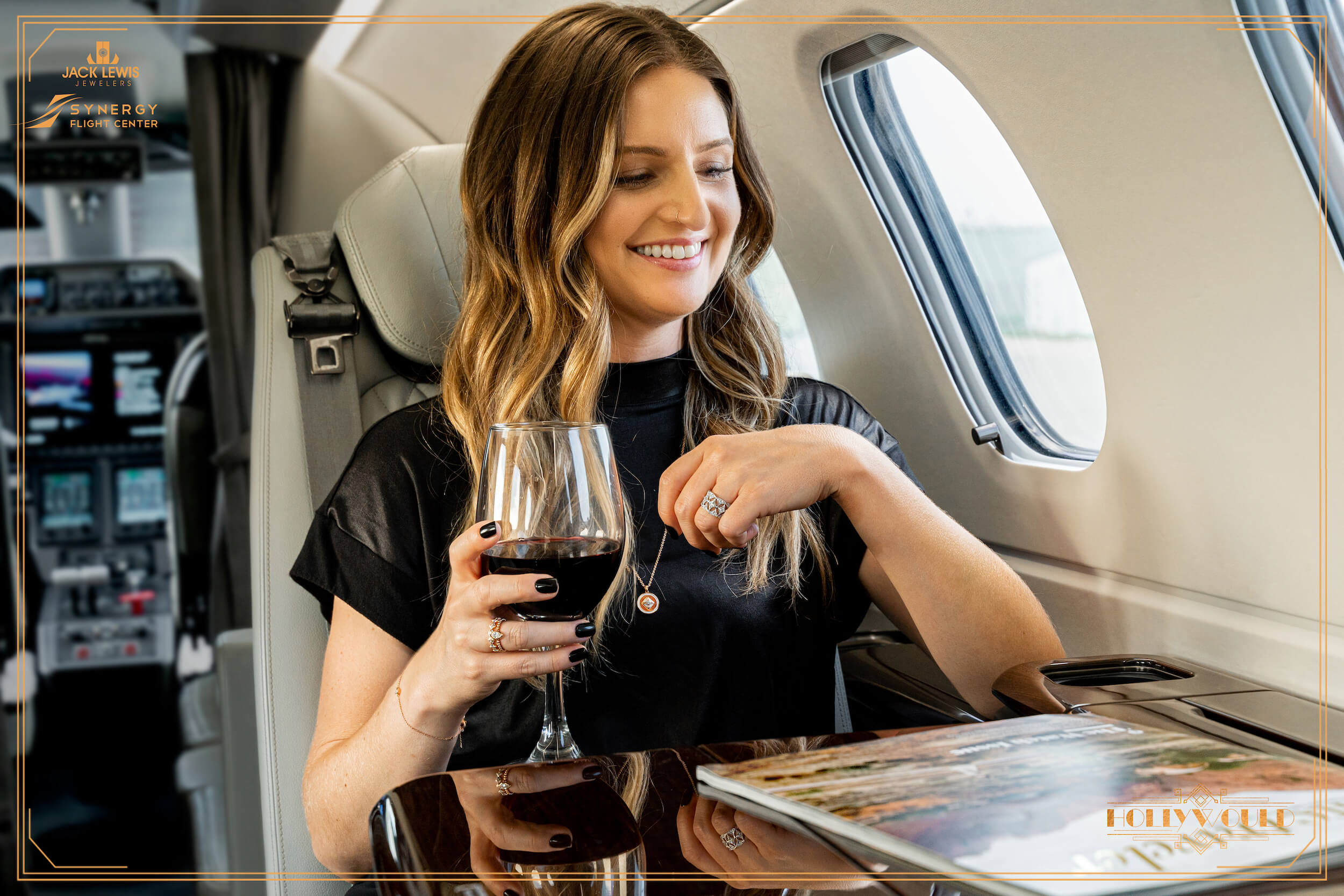Young woman with long brown hair seated in a private jet at the Synergy Flight Center in Bloomington Illinois. She is drinking  a glass of red wine and smiling while looking out the airplace window. Jewelry by Debeers Forevermark is clearly in view.