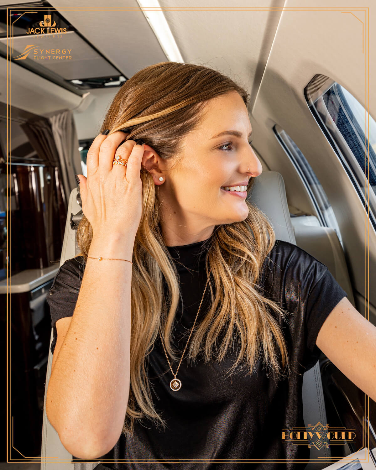 A young woman with long brown hair pulls her hair back to reveal a diamond stud earing and you can see the diamond rings and bracelet she is wearing all from Debeers Forevermark. She is sitting in a private yet from Synergy Flight Center in Bloomington Illinois and smiling as she looks out the window.