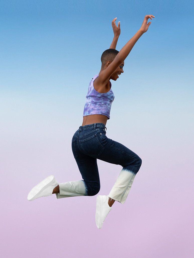 A young woman jumping in the air, arms raised, wearing clean white shoes and jeans