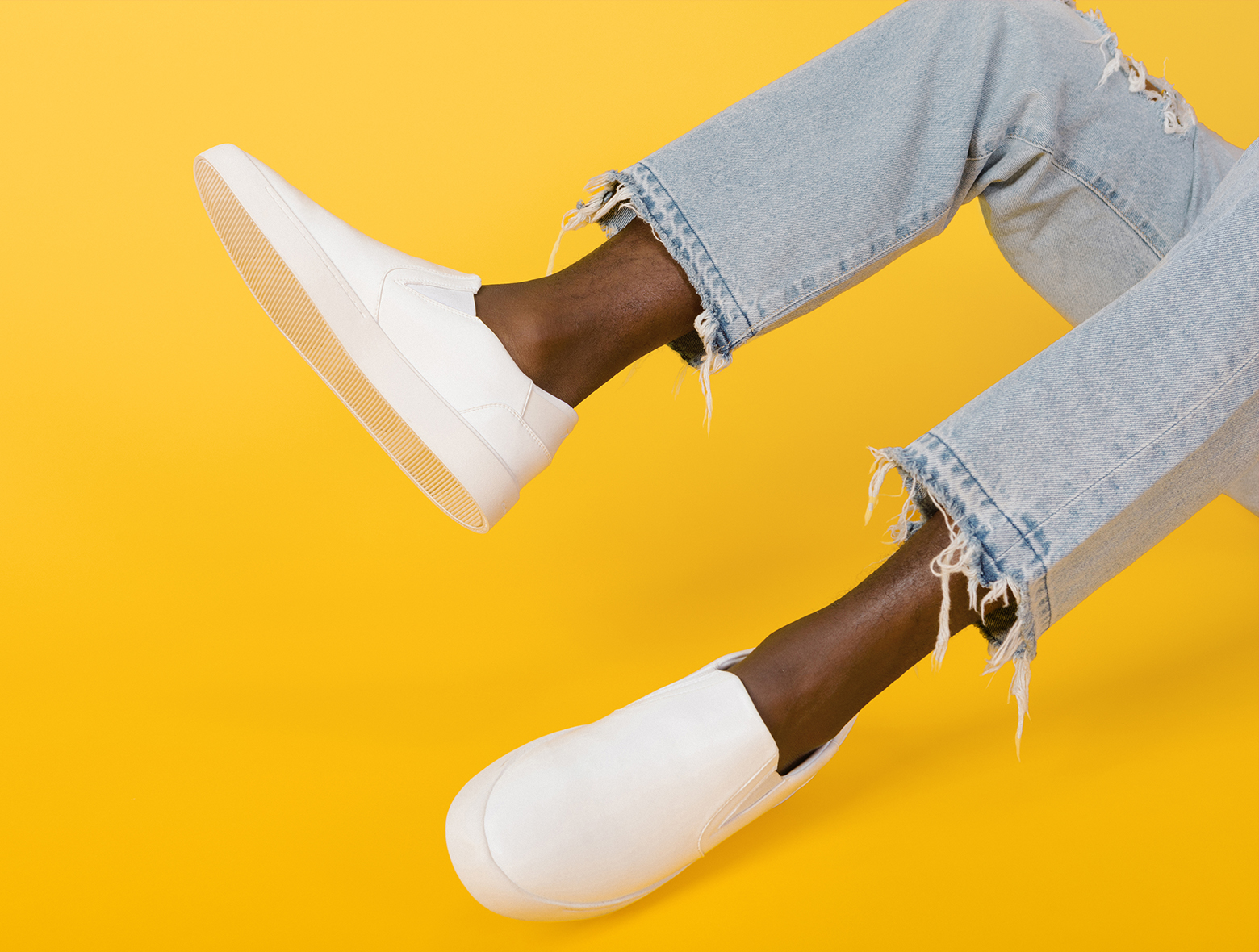 Crisp white sneakers on a bright yellow backdrop