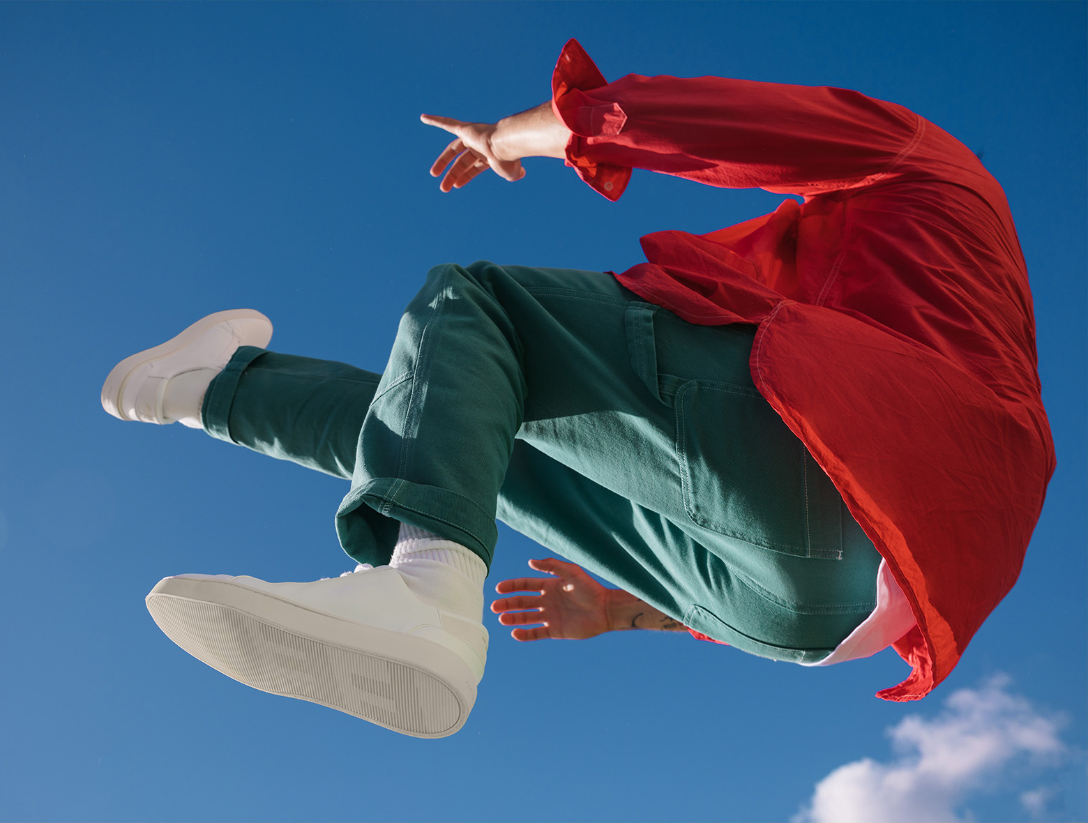 One final image of a young man falling through the sky wearing crisp, white sneakers