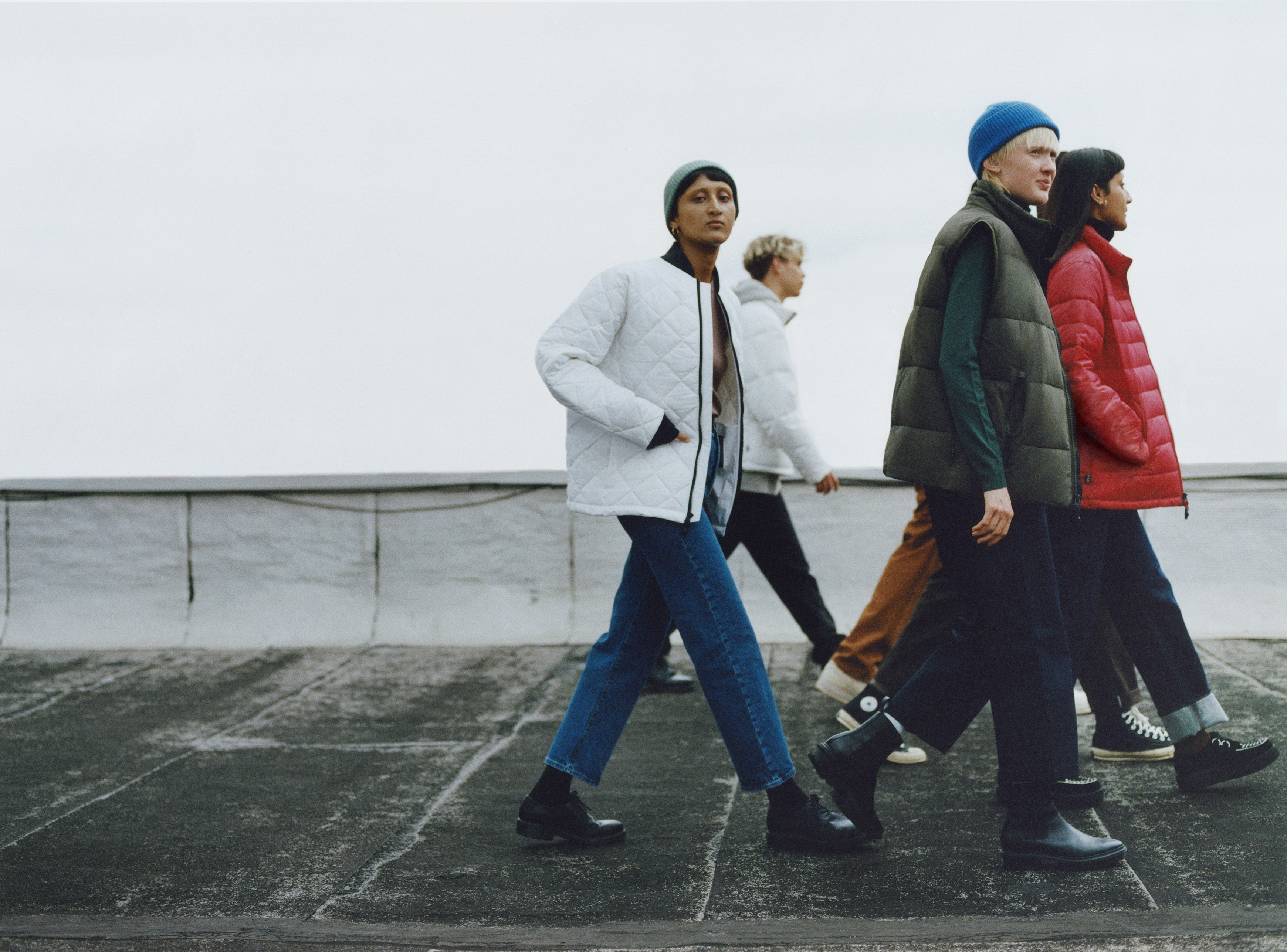 A gang of young people wearing large colorful jackets walking around a cityscape