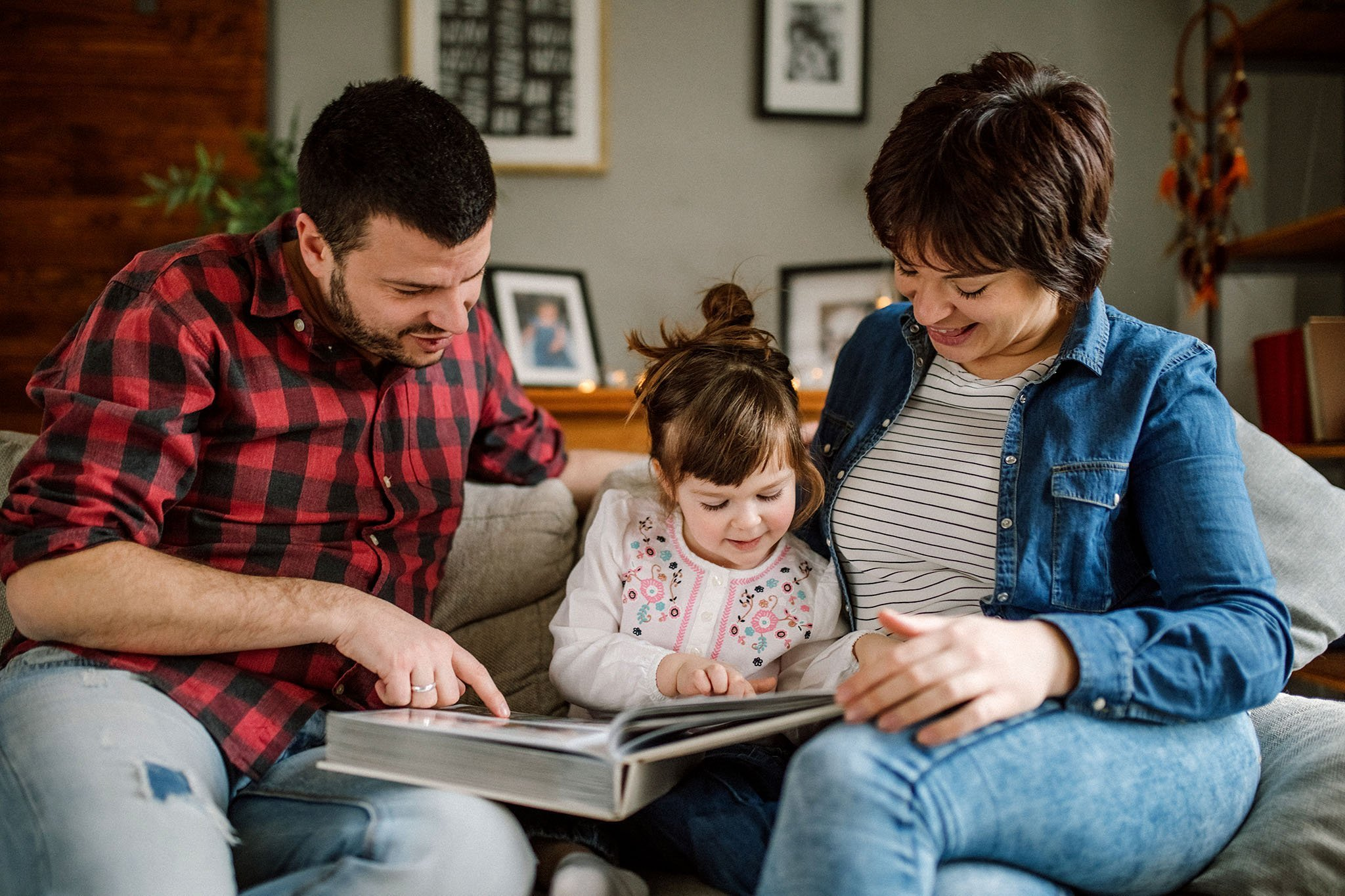 Couple looking at photo album with child