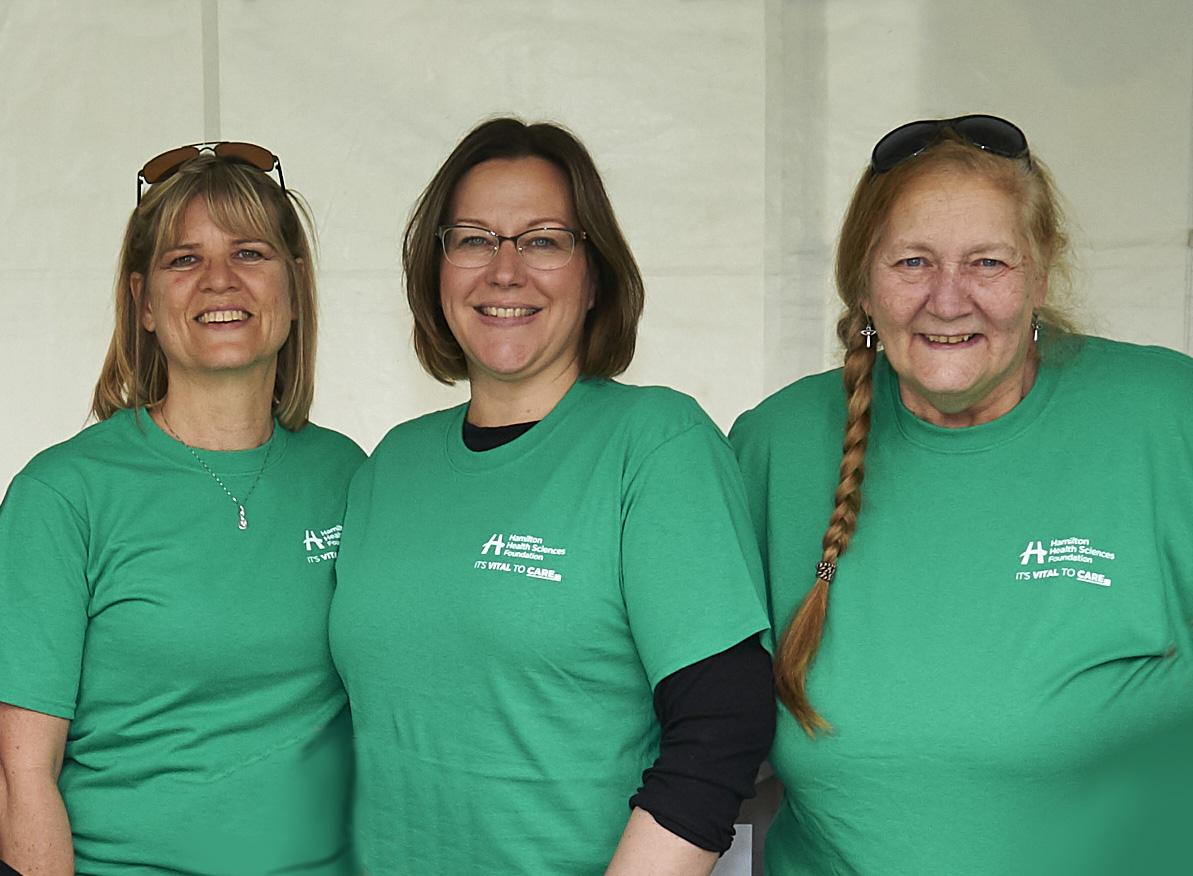 Three event volunteers smile at camera