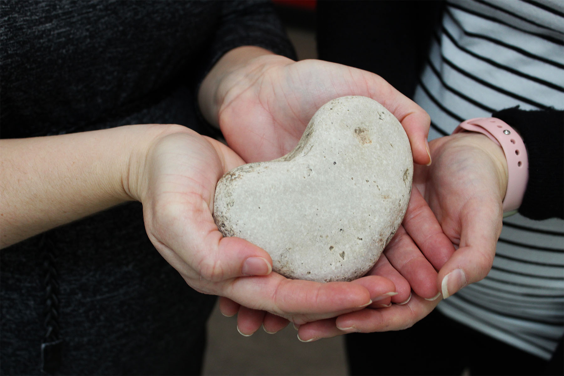 Hands holding a heart-shaped rock