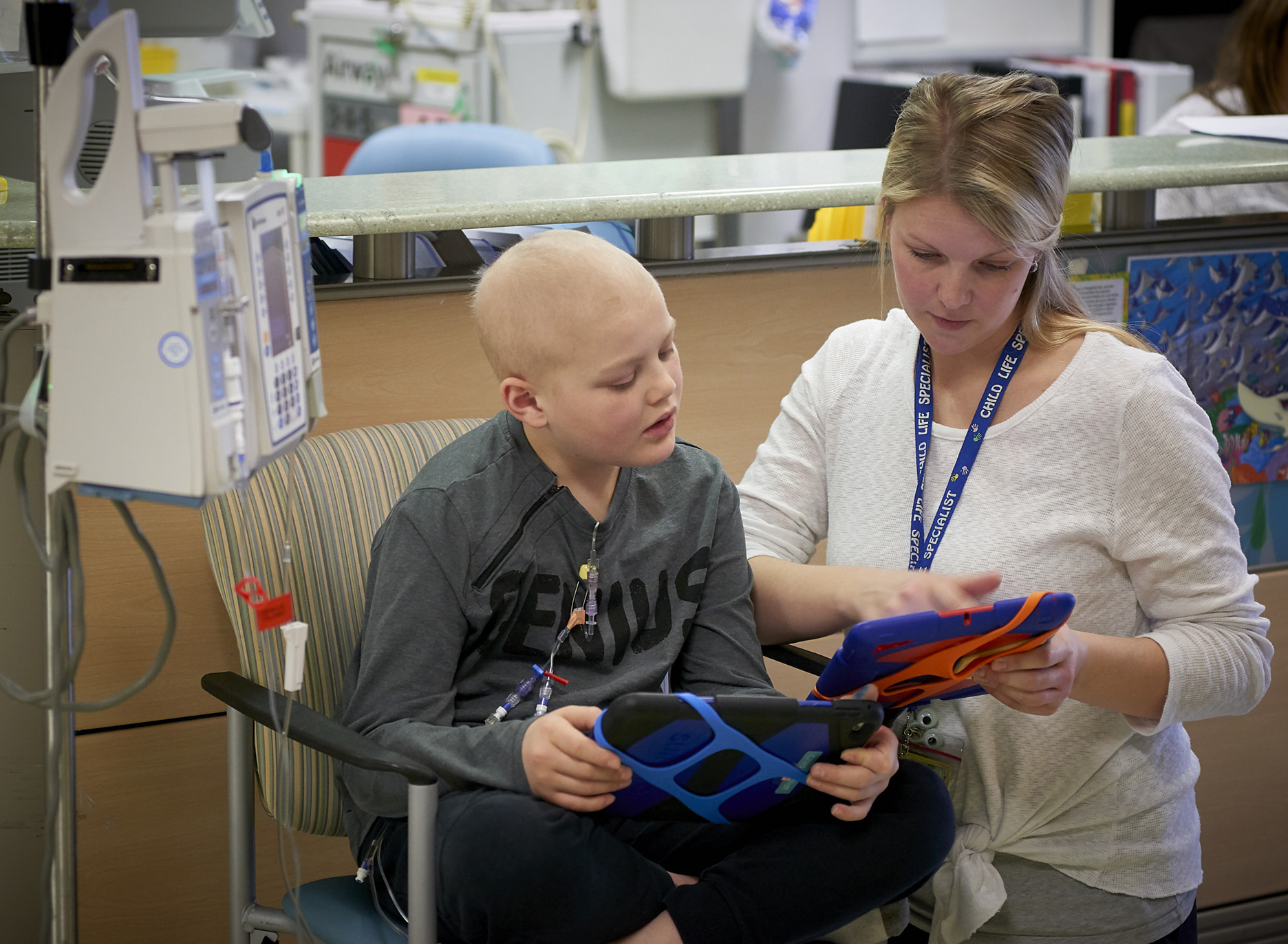 A child patient reads with a caregiver