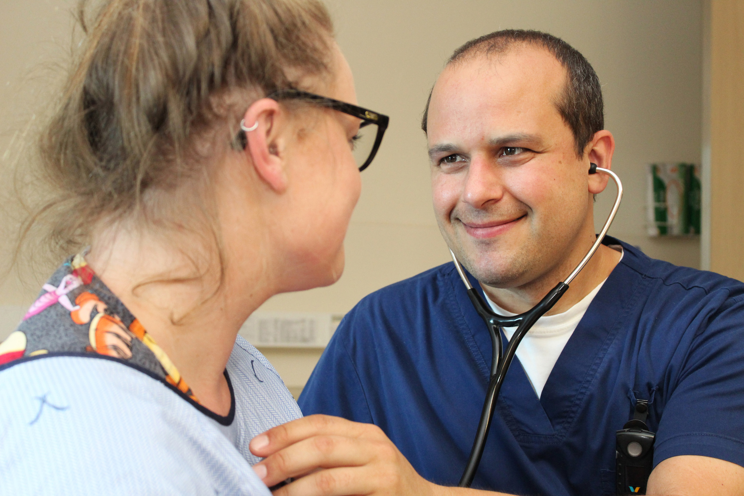 A caregiver is using a stethoscope on a patient