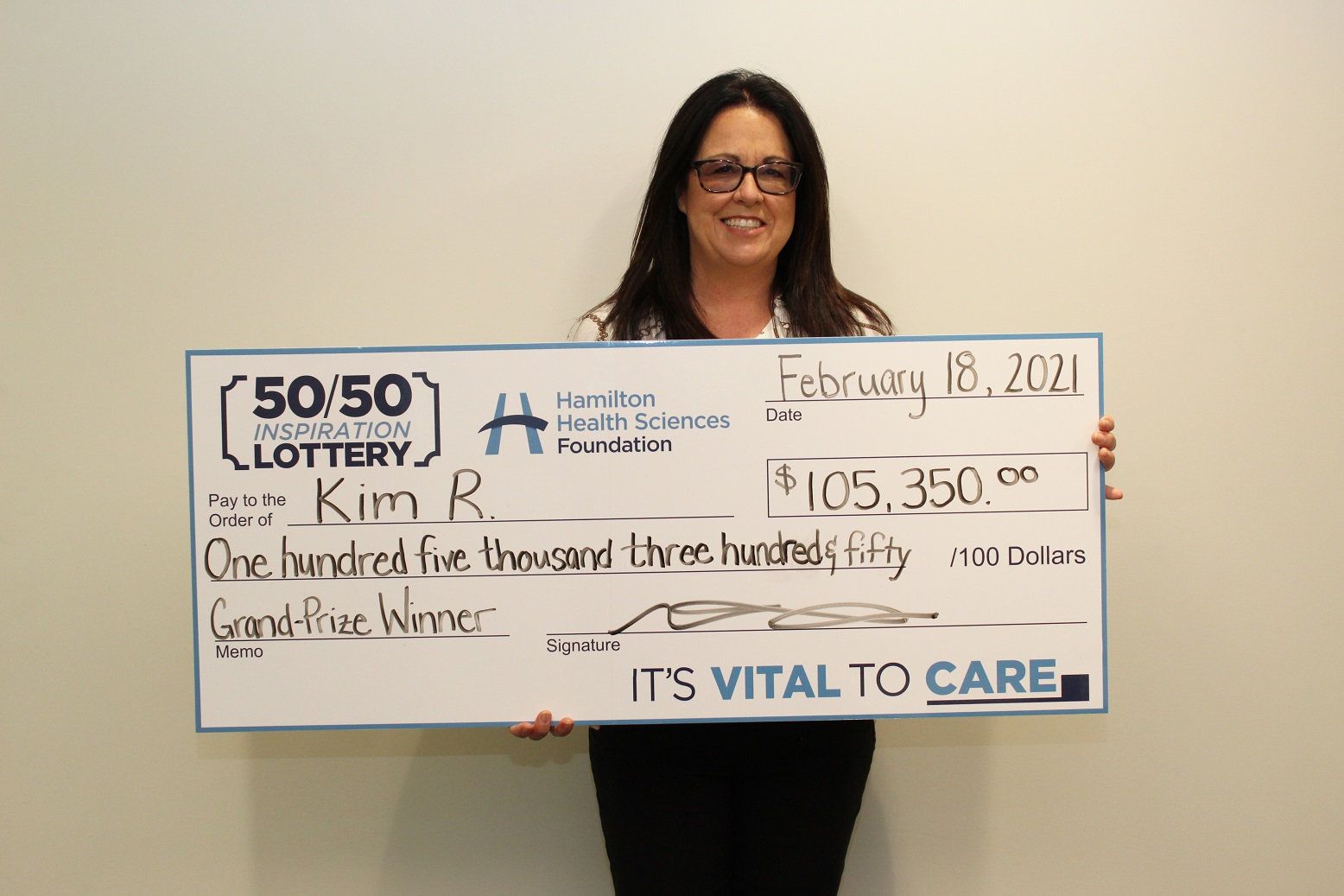 The lottery winner holds a big cheque.