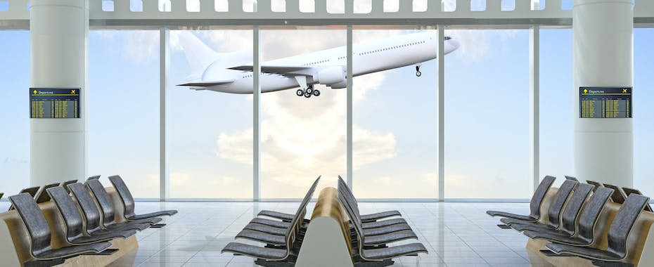Plane taking off outside window of empty airport