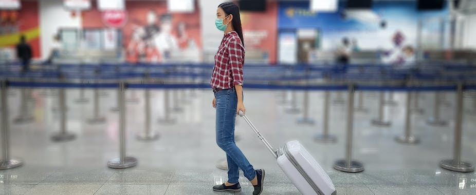 Lone traveler wearing face mask pulling suitcase in empty airport queue