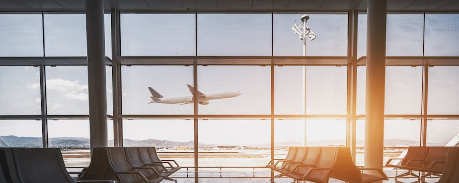 Plane taking off outside window of empty airport seats