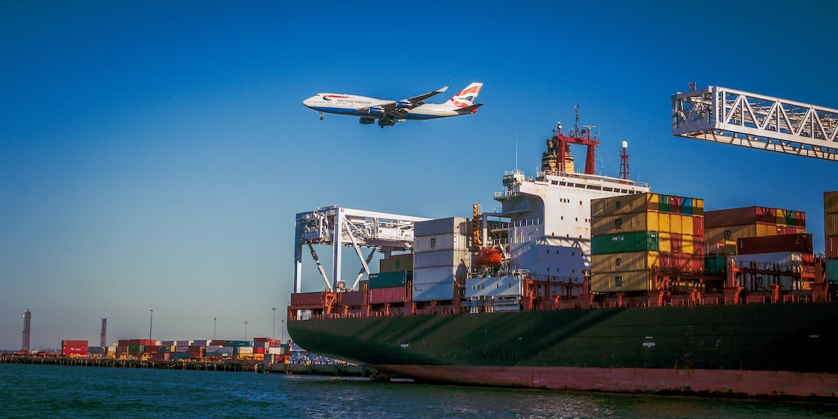 Low-flying airplane over container ship