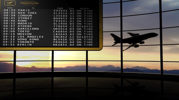 Departure times with airplane taking off in the background