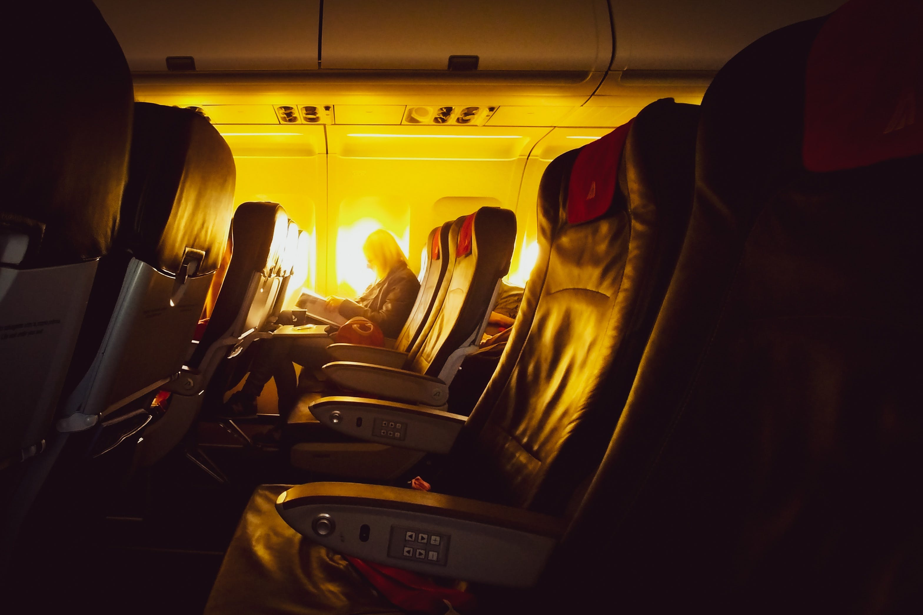 Row of airline seats with lone passenger reading a book