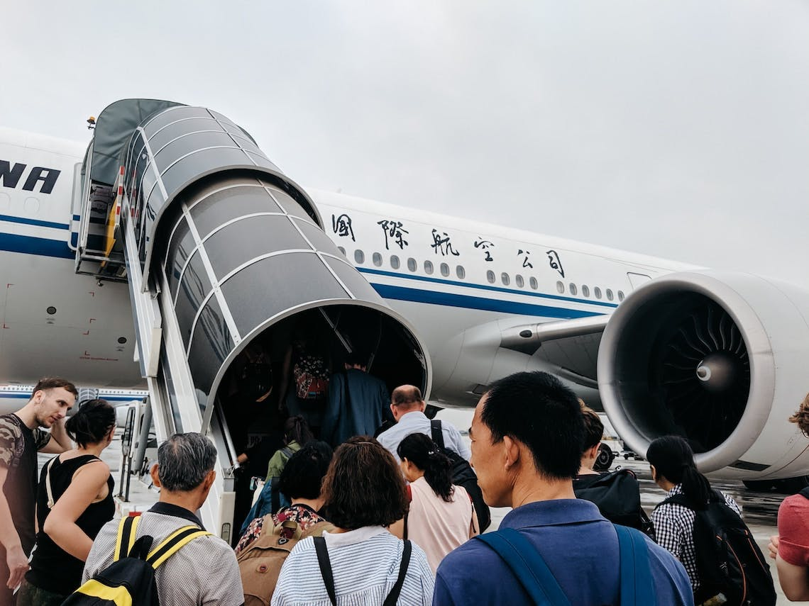 Crowd of passengers boarding airplane from tarmac