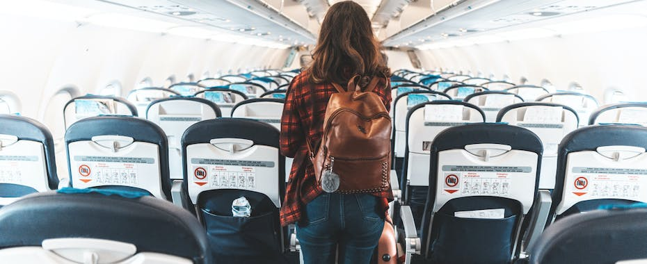 Ariline passenger walking towards exit of empty airplane