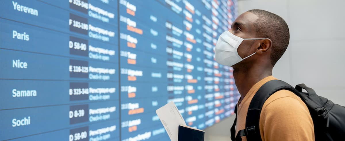 Traveler with facemask at airport checking flight schedules