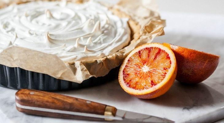 Tarte à la crème avec un agrume et un couteau à coté.