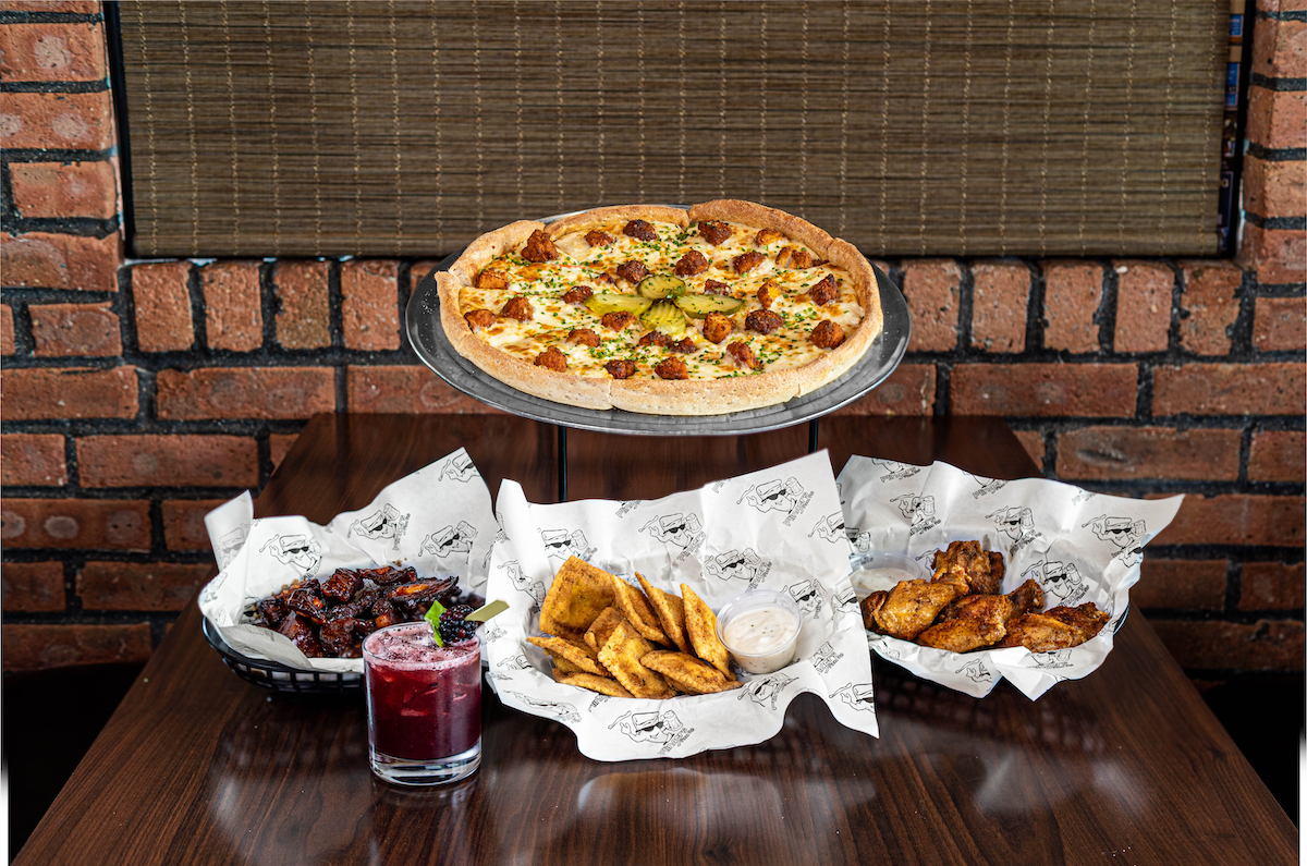 All items are on a wooden table inside Flingers Pizza Pub. In the back is the Party Fowl Pizza on a silver platter. In the front left is a basket of Chipotle Honey BBQ Rib Tips, with a basket of Jalapeño Popper Toasted Ravioli to the right of that, and a basket of bone-in Texas Dust Wings on the far right. In the very front is a purple cocktail, the Bourbon Smashville with a blackberry on the top.