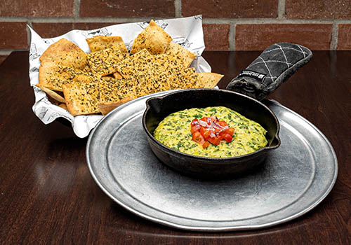 spinach dip with pizza chips in a small skillet