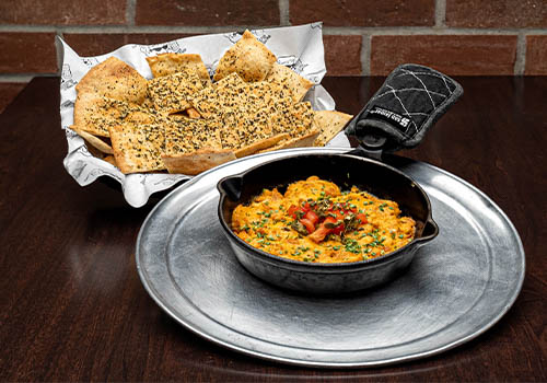 buffalo dip with pizza chips in a small skillet