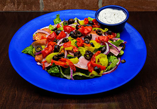 Pub salad including black olives, pepperoni, bana peppers, and more