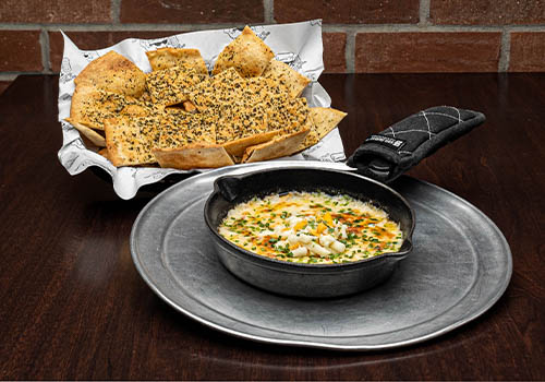 beer cheese bacon dip with pizza chips in a small skillet