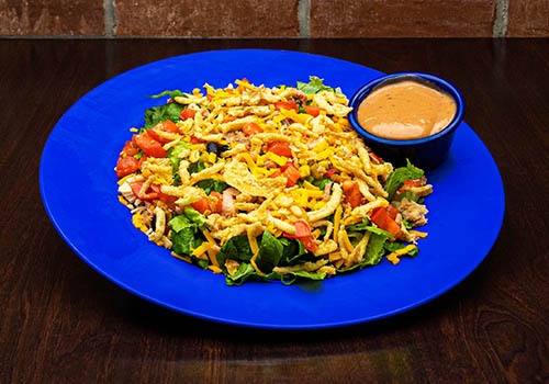 a salad including smoked chicken, onion crisps, chopped tomatoes, cheddar cheese, and more