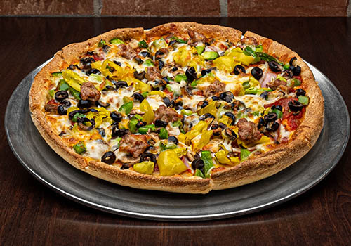 craft supreme pizza topped with sausage, bacon, banana peppers, black olives, and more