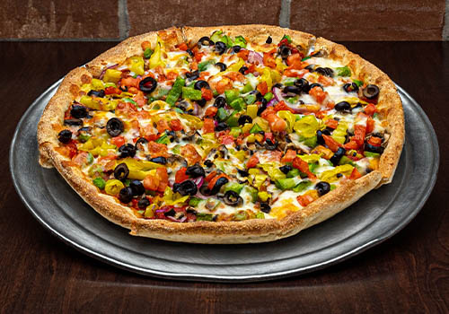 craft veggie pizza topped with black olives, bannana peppers, tomatoes, onions, and more