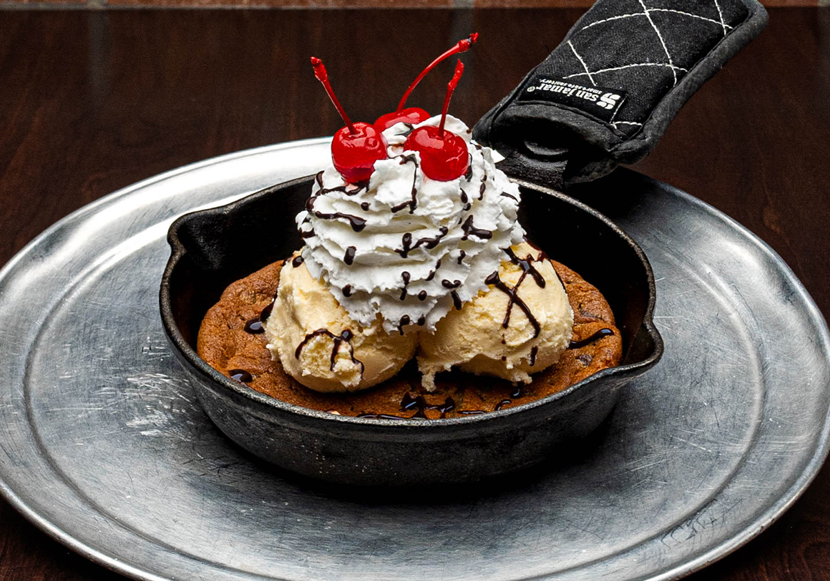 Skillet cookie topped with two scoops of vanilla ice cream and whipped cream