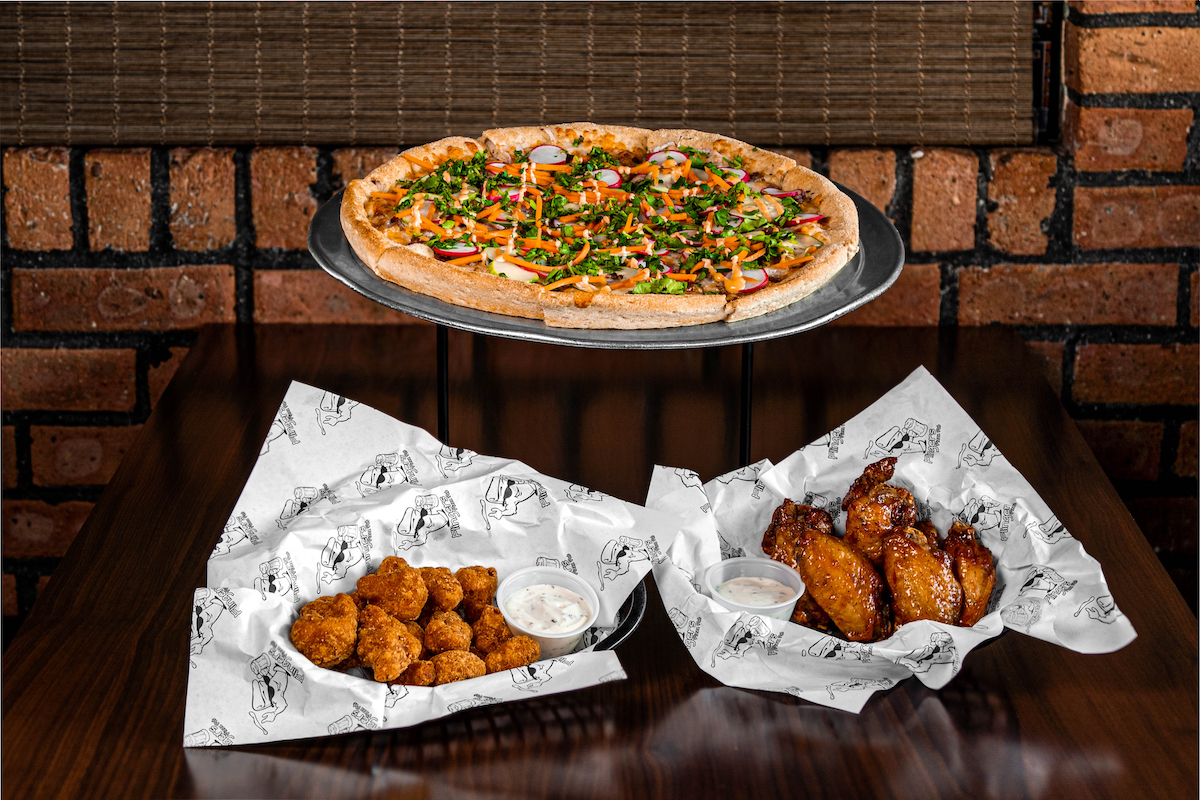 The Banh Mi Pizza on a silver platter, next to a basket of Spicy Cauliflower Bites and a basket of Asian Ginger Wings on a table top inside Flingers Pizza Pub.