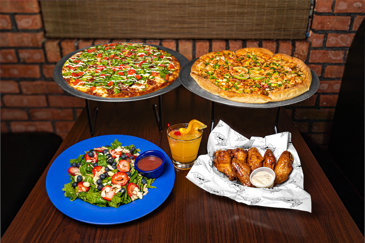 Items set on a table inside Flingers Pizza Pub. In the background is the Total Jerk Pizza on a silver platter on the right, next to a BLT Bomb on a silver platter on the left. In the front left is the Liberty Salad in a blue bowl, topped with strawberries and blueberries. In the front center is a low ball glass with the cocktail, Tropic Like It's Hott, topped with a cherry and orange slice. In the front right is a basket of bone-in  Castaway Glaze Wings.