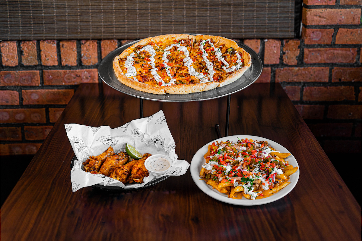 Items set on a table inside Flingers Pizza Pub. In the background is the Desperado Pizza on a silver platter.  In the front left is a basket of Chili-Lime Dry Rub Wings with a lime wedge and side of ranch. In the front right is a plate of basket of Street Taco Fries.