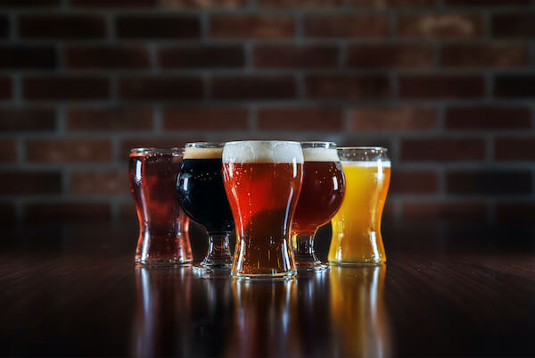 pizza of several small glasses of beer that are all different shades of yellow, orange and red