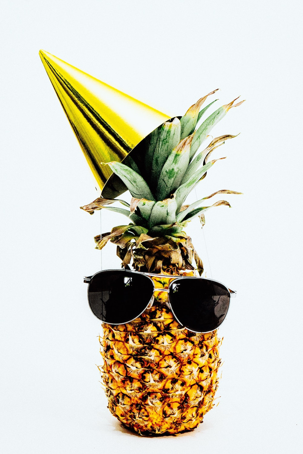 Pineapple with sunglasses and a party hat