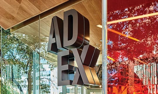 AD EX dimensional signage identity mounted to glass facade of architecture.