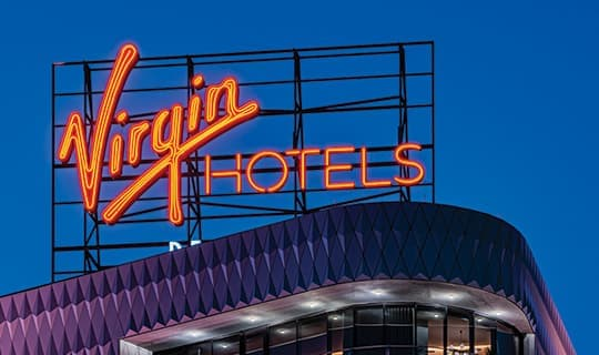 Geometric hotel architecture with neon rooftop identity signage.